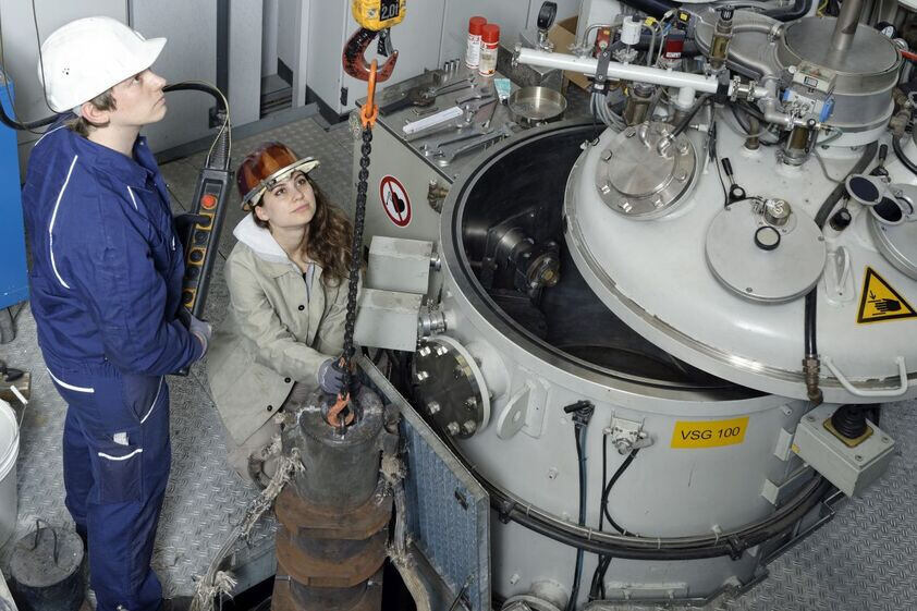 Researchers in front of a large machine